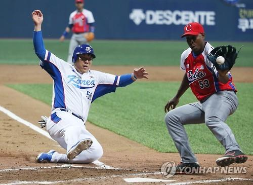 Kim Hyun-soo of South Korea (L) scores on a wild pitch by Cuba's Danny Betancourt (R) in the bottom of the fifth inning at Gocheok Sky Dome in Seoul on Nov. 4, 2015. (Yonhap)