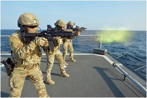 Three Navy SEALs pose for a photo as they recall the Navy anti-piracy unit