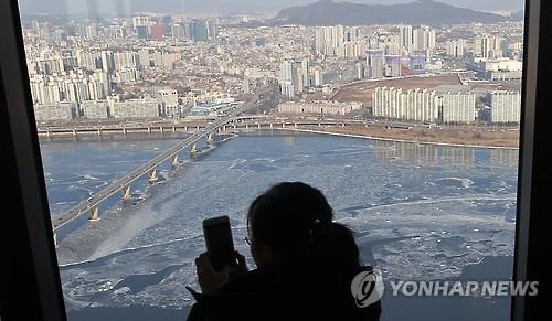 A Seoul citizen takes a photo of ice on the Han River on Jan. 24. (Yonhap)