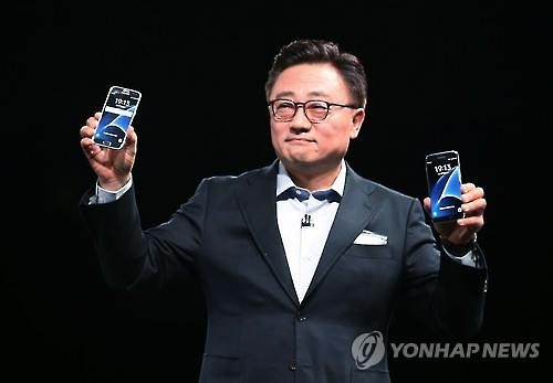 Koh Dong-jin, who heads Samsung Electronics Co.'s mobile communications business, holds the Galaxy S7 smartphones in a showcase event held on Feb. 21, 2016 in Barcelona, Spain.                                                                                                                           (Yonhap)