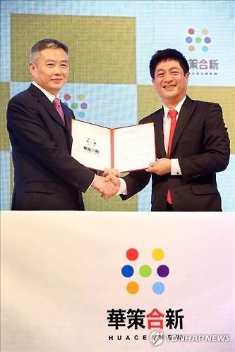 """Kim Woo-taek (R), CEO of the South Korean film studio NEW, shakes hands with a vice president of China's Huace Media Group during a ceremony to mark the launch of a Beijing-based joint venture """"Huace & New"""" at  the Busan International Film Festival on Oct. 5, 2015. (Yonhap)"""