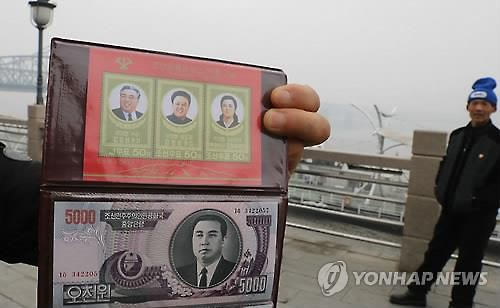 A Chinese vendor shows souvenir North Korean bills near a bridge over the Amrok River in the Chinese border city of Dandong in this photo taken on March 3, 2016, following the United Nations Security Council's adoption of a fresh resolution punishing North Korea for its nuclear test. Officials at Chinese banks in border areas said they were ordered to suspend transactions with North Korean banks. (Yonhap)