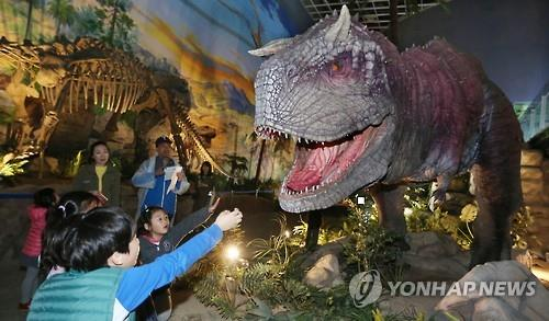 Kids try to touch a life-size replica of a dinosaur at the Gyeongnam Goseong Dinosaur World Expo scheduled to last through June 12, 2016. (Yonhap)