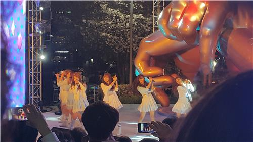 South Korean girl group Lovelyz performs on the dance stage in front of the Gangnam Style bronze sculpture in the eastern patio of COEX in the Gangnam Ward of southeastern Seoul on April 15, 2016. (Yonhap)