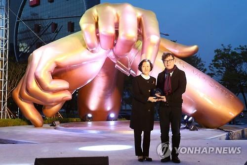 Gangnam Ward chief Shin Yeon-hee (L) and designer Hwang Man-suk, who designed the Gangnam Style bronze sculpture, pose in the eastern patio of COEX in Gangnam Ward, southeastern Seoul, on April 15, 2016. (Yonhap)