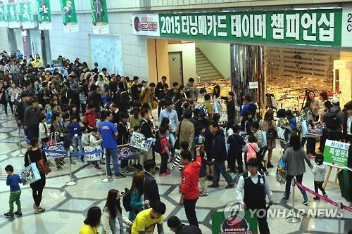Parents and kids stand in a long line to participate in a game event involving the Turning Mecard toy series, organized by Sonokong Co., at the COEX Convention Center in downtown Seoul, on Oct. 24, 2015 (Yonhap file photo)