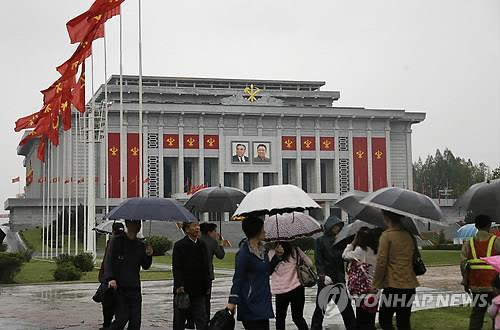 North Koreans with umbrellas walk near the April 25 House of Culture in Pyongyang on May 6, 2016, where the congress by the Workers' Party of Korea was held, in this photo released by the Associated Press. (For Use in South Korea Only & No Redistribution) (Yonhap)