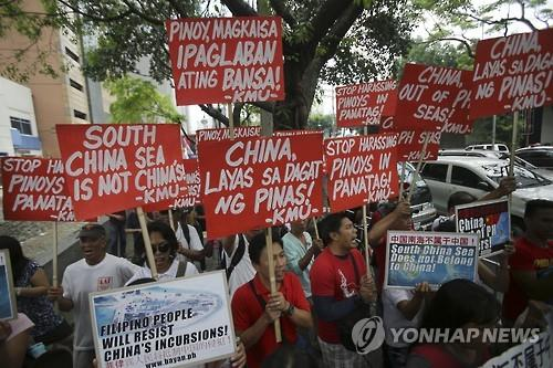 Filipino activists holding banners march toward the Chinese Consulate during a rally in the financial district of Makati, south of Manila, on June 4, 2015 to denounce China's claim over most of the South China Sea, in this photo released by the Associated Press. (Yonhap)