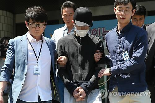 A 34-year-old man, who is accused of stabbing a 23-year-old woman to death in Gangnam district, Seoul, is flanked by police officers as he leaves the Seocho Police Station in Seoul on May 19, 2016, to attend a hearing for his arrest warrant. The Seoul Central District Court issued the warrant, saying he could possibly try to destroy evidence or flee. (Yonhap)