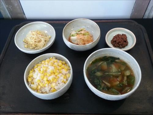 This photo shows a simple meal for ordinary North Koreans that consists of steamed maize mixed with rice, soup and three side dishes, including kimchi and seasoned soybean sprouts. (Yonhap)