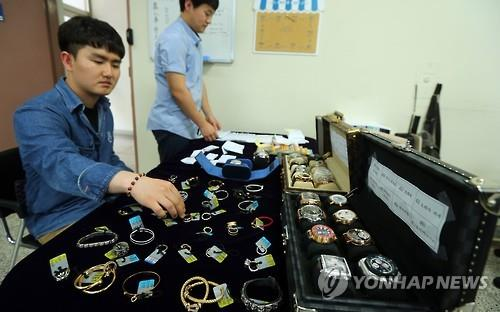 In this photo taken on June 15, 2016, police officers from the Geoje Police Station in South Gyeongsang Province display luxury goods confiscated from a former Daewoo Shipbuilding employee who embezzled 18 billion won in company funds over eight years. (Yonhap)