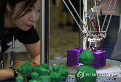 A woman watches how a 3D printer makes a product at the Inside 3D Printing Conference & Expo held at the KINTEX exhibition center in Goyang, Gyeonggi Province, on June 23, 2016 (Yonhap)