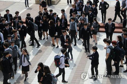 Star go player Lee Se-dol and his daughter (center) show up at an international school in Jeju Island on March 17, 2016. (Yonhap)