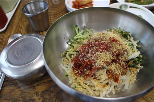 "A bowl of ""mulhoi,"" or ""water sushi"" made with raw squid, is served at a restaurant on Ulleung on June 28, 2016. (Yonhap)"