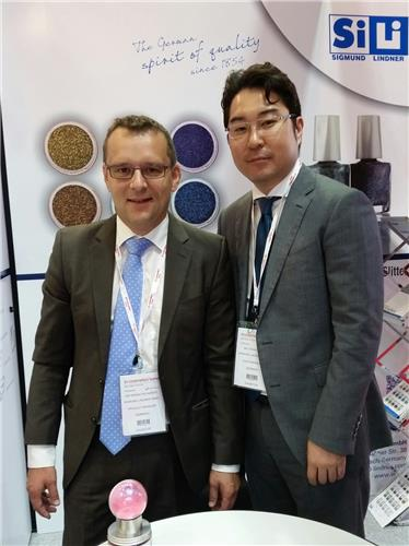This photo taken on July 7, 2016, Erwin Pschierer, head of product management at Sigmund Lindner GmbH, poses for a photo with his Korean colleague in the company's booth during the 'in-cosmetics Korea' exhibition held in Seoul on July 6-7. (Yonhap)