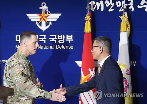 The defense ministry's deputy minister for policy Yoo Jeh-seung (R) shakes hands with USFK Chief of Staff Lt. Gen. Thomas Vandal at a news conference in Seoul on July 8, 2016. The two allies agreed to deploy the THAAD defense system in South Korea. (Yonhap)