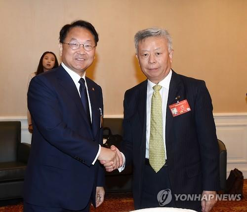 South Korea's Finance Minister Yoo Il-ho (L) shakes hands with AIIB President Jin Liqun in Beijing on June 25, 2016. (Courtesy of the finance ministry)
