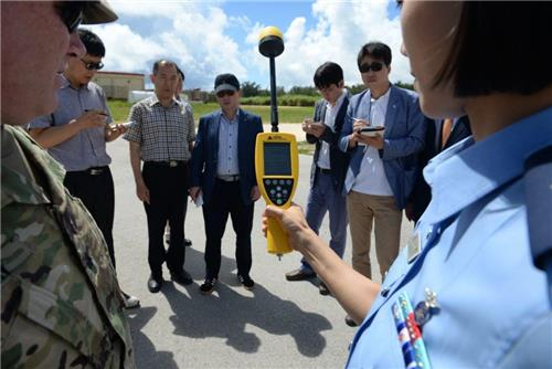 This photo, taken on July 18, 2016, and provided by the U.S. Air Force, shows officials measuring the level of electromagnetic waves from the radar of a THAAD battery in Guam, with South Korean reporters watching and taking notes. (Yonhap)