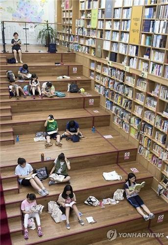 Citizens read books on the stairs of a city-run library in central Seoul on July 19, 2016, as the daytime high was forecast to soar to 32 degrees Celsius in the capital area. (Yonhap)