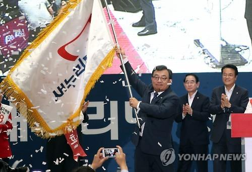 New Saenuri Party leader Lee Jung-hyun waves the party's flag during the party's national convention at Jamsil Indoor Stadium in Seoul on Aug. 9, 2016. (Yonhap)