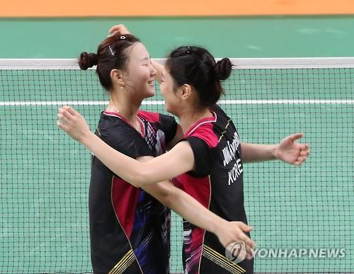 South Korean badminton players Shin Seung-chan (L) and Jung Kyung-eun embrace each other after clinching bronze in the women's doubles at the Rio de Janeiro Olympics on Aug. 18, 2016. (Yonhap)