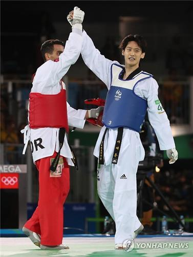 Lee Dae-hoon of South Korea raises the hand of Ahmad Abughaush of Jordan after losing to him in the quarterfinals of the men's -68kg taekwondo at the Rio de Janeiro Olympics on Aug. 18, 2016. (Yonhap)