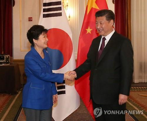 This photo, taken on April 1, 2016, shows President Park Geun-hye (L) shaking hands with her Chinese counterpart Xi Jinping before their talks on the sidelines of the Nuclear Security Summit in Washington, D.C. (Yonhap)