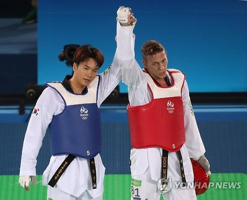 Cha Dong-min of South Korea (L) and Dmitriy Shokin of Uzbekistan raised their arms after Cha's victory in the bronze medal contest in the men's 80kg taekwondo at the Rio de Janeiro Olympics on Aug. 20, 2016. (Yonhap)