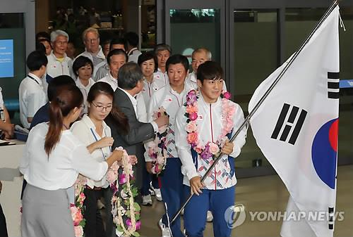 The South Korean delegation to the Rio de Janeiro Olympics, led by the national flag bearer and wrestler Kim Hyeon-woo (R), walk through Incheon International Airport, west of Seoul, after they returned home from Brazil on Aug. 24, 2016. (Yonhap)