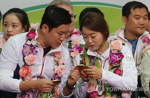 South Korean shooter Jin Jong-oh (L) touches archer Chang Hye-jin's Olympic gold medal during a ceremony to disband the South Korean delegation to the Rio de Janeiro Olympics at Incheon International Airport, west of Seoul, on Aug. 24, 2016. (Yonhap)