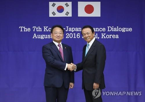 South Korea's Finance Minister Yoo Il-ho (L) shakes hands with his Japanese counterpart Taro Aso at the Seoul-Tokyo finance ministers' meeting in Seoul on Aug. 27, 2016. (Yonhap)