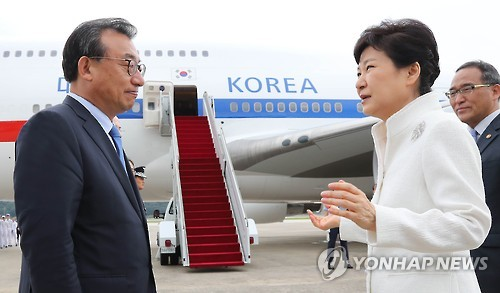 President Park Geun-hye (R) talks with Saenuri Party leader Lee Jung-hyun before boarding her plane at a military airport in Seongnam, south of Seoul, on Sept. 2, 2016. (Yonhap)
