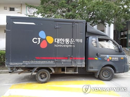 This undated photo shows a parcel delivery truck of CJ Korea Expresses passing by an apartment in Seoul. (Yonhap)