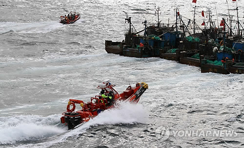 In this photo provided by the Korea Coast Guard, a Korean speedboat moves in on Chinese fishing boats in South Korea's territorial waters in the West Sea on Dec. 27, 2012. (Yonhap)