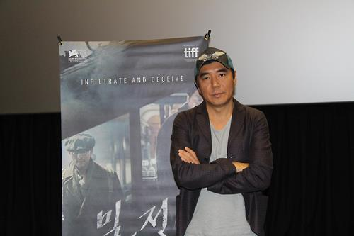 "Kim Jee-woon, director of potential Oscar contender ""The Age of Shadows,"" stands in front of a poster of his film. (Yonhap)"