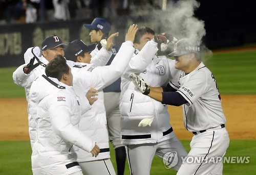 Oh Jae-il of the Doosan Bears (R) is congratulated by his teammates after hitting a game-winning sacrifice fly against the NC Dinos in Game 1 of the Korean Series at Jamsil Stadium in Seoul on Oct. 29, 2016. (Yonhap)