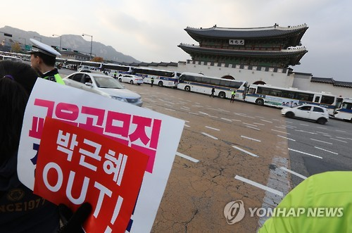 """A citizen holds a picket that says """"Park Geun-hye Out"""" in front of barricades made of police buses in central Seoul on Nov. 12, 2016, during a massive rally to demand the president's resignation over the latest influence-peddling scandal involving her confidante. (Yonhap)"""