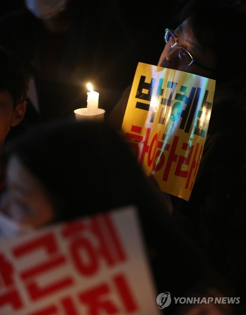 A protester holds up a candle during a rally in the city of Jeju on South Korea's largest island of the same name on Nov. 12, 2016, to call for President Park Geun-hye's resignation over an influence-peddling scandal implicating her longtime close friend Choi Soon-sil. (Yonhap)