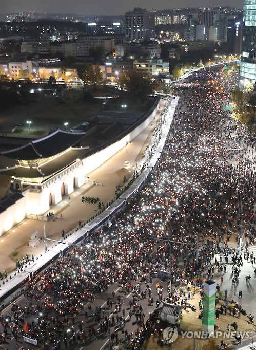 Protesters stage a candlelight rally in front of the Gyeongbok Palace in downtown Seoul on Nov. 12, 2016, to call for President Park Geun-hye's resignation over an influence-peddling scandal implicating her longtime close friend Choi Soon-sil, as police block their way to the presidential office by setting up a barricade made of police buses. (Yonhap)