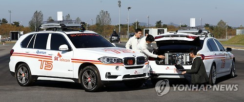 Officials from South Korean telecommunications giant SK Telecom and German automaker BMW tune their jointly developed connected car, the T5, before a test run at a BMW driving center in Incheon, South Korea, on Nov. 15, 2016. (Yonhap)