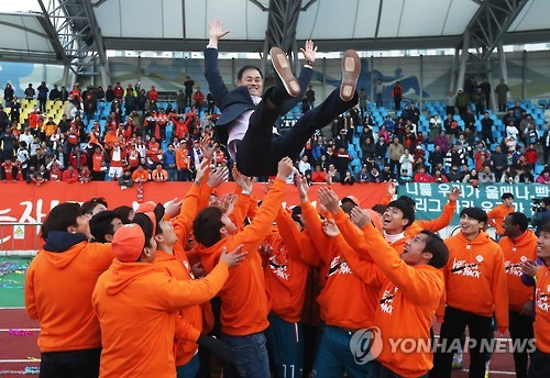 Gangwon FC head coach Choi Yun-kyu is tossed in the air by the players at Tancheon Stadium in Seongnam, Gyeonggi Province, on Nov. 20, 2016, after Gangwon edged out Seongnam FC to earn promotion to the first division K League Classic next season. (Yonhap)