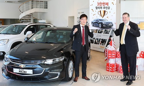 Dale Sullivan (R), vice president of vehicle sales, service and marketing at GM Korea, poses for a picture with a South Korean customer, who purchased the 30,000th unit of the All New Malibu sold in South Korea on Nov. 16, 2016. (Photo courtesy of GM Korea)