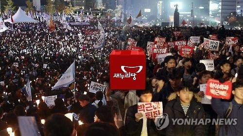 Prostesters hold the logo of the ruling Saenuri Party. (Yonhap)