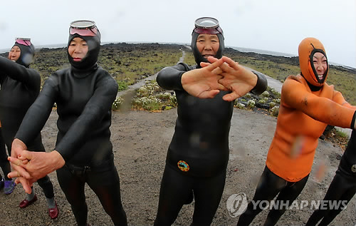 A group of haenyeo warm up before diving into waters off Jeju Island on May 14, 2014. (Yonhap)
