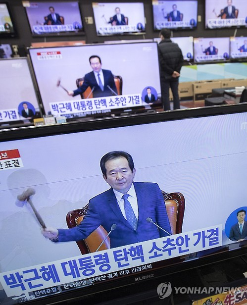 Television sets lined up for display at Yongsan ETLand in Seoul are all tuned to the live broadcast from the National Assembly on the results of a vote on the impeachment motion against President Park Geun-hye on Dec. 9, 2016. The motion was passed 234 to 56 in a vote by 299 lawmakers, with two abstentions and seven invalid votes. (Yonhap)