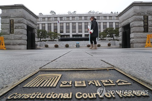 A pedestrian walks past the Constitutional Court in Seoul on Dec. 26, 2016. The court said it will be able to start its official review of the impeachment of President Park Geun-hye next week, having secured investigation results from the prosecution on the same day. The parliament on Dec. 9 voted in an overwhelming majority to impeach Park who is implicated in influence peddling allegations against her confidante. (Yonhap)