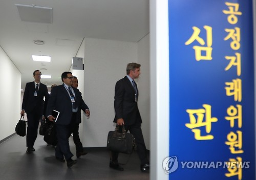 Qualcomm officials enter a courtroom of the Fair Trade Commission in Sejong central South Korea on Dec. 28 2016