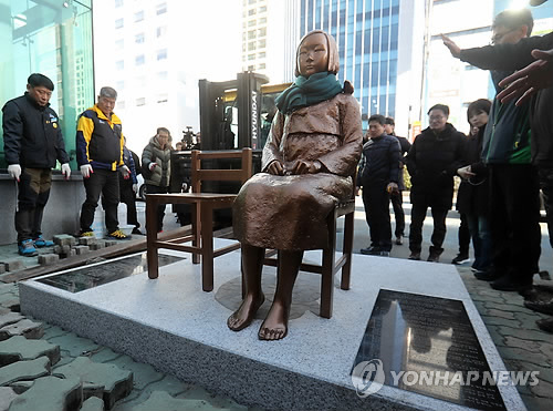 This photo, taken on Dec. 30, 2016, shows people installing a statue of a girl representing victims of wartime sex slavery by the Japanese military in front of the Japanese Consulate in South Korea's largest port city of Busan. (Yonhap)