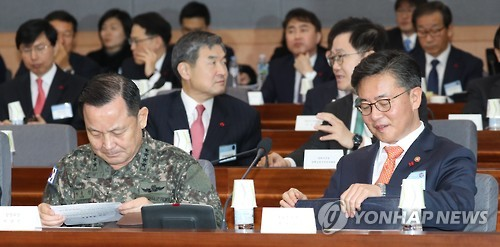 Unification Minister Hong Yong-pyo (R) looks at reports in the government's 2017 policy briefing on defense and diplomatic affairs held at the government complex building in central Seoul on Jan. 4, 2016. (Yonhap)
