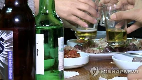 This undated photo captured from Yonhap News TV shows people toasting with beer and soju, a distilled beverage made of ethanol and water. (Yonhap)